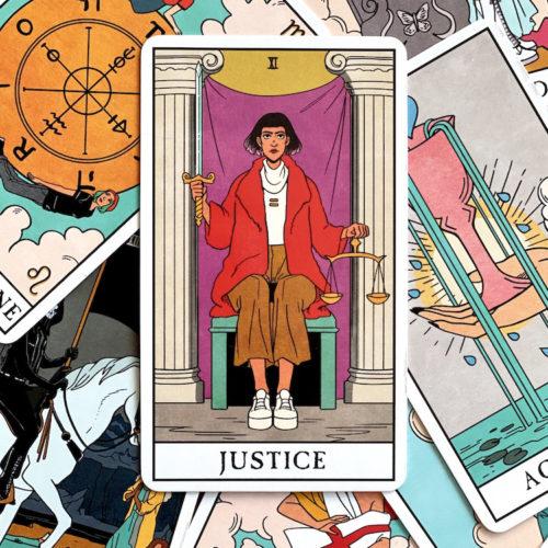 Justice tarot card on top of pile of Modern Witch tarot deck tarot cards