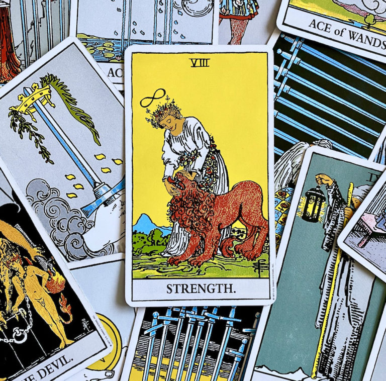 Strength Card on top of pile of Rider Waite Smith tarot cards
